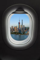 Shanghai, China - May 23, 2018: Sunset view of the modern Pudong skyline in in airplane window