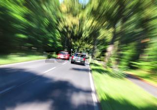Landstraße mit PKW in Bewegungsunschärfe