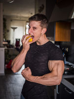 Young muscular man eating an apple in kitchen