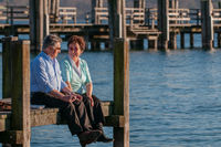 Happy senior couple sitting at the waterfront