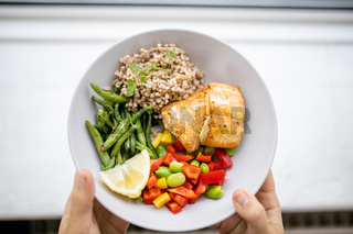Hands holding salmon and buckwheat dish with green beans
