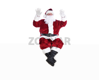 Senior man in traditional Santa Claus Suit sitting on a white wall with both hands in the air.