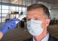 Senior man wearing face mask having temperature taken to check for virus at airport