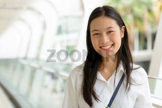 Young beautiful Asian businesswoman at the footbridge
