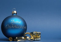 Blue vintage Christmas baublewith the German words Merry Christmas