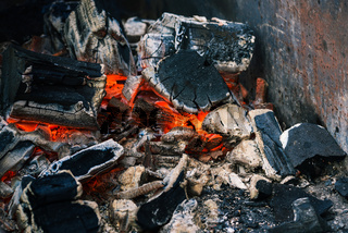 Coal in the fireplace. Extinguishing bonfire after burning wood. Cooking on fire. Smoldering charcoal