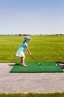 Little girl learning to play golf