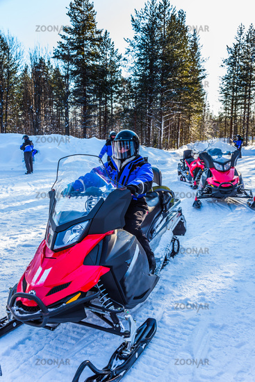 Tourist snowmobiles moves along the ice
