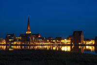 Blick über die Warnow auf die Hansestadt Rostock zur Blauen Stunde
