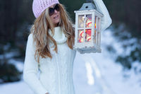 Woman holding a lantern of fairy lights and Christmas baubles