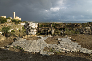 Pillar and ancient street in sunlight during storm in ruins with dramatic cloudscape in Tyre, Sour, Lebanon