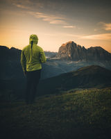 man standing on mountain peak in dolomites during sunrise