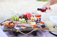 Man pouring wine having picnic on beach