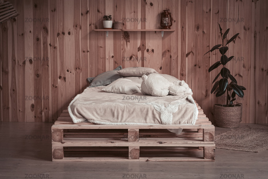 Simple cozy bed in wooden apartment. Front view. Comfortable place or space for rest