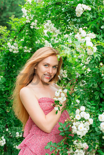 woman stands near a garden of white roses