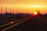 An intense golden sunset over the railroad tracks at dusk