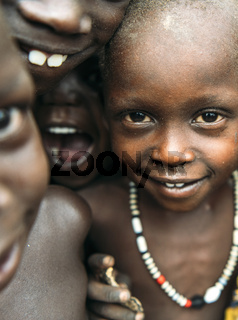 TOPOSA TRIBE, SOUTH SUDAN - MARCH 12, 2020: Children of Toposa Tribe smiling and looking at camera while playing together in village in South Sudan, Africa