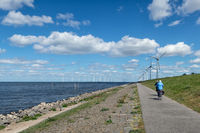 Dutch dike along IJsselmeer with senior cyclists and wind turbines