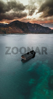 Traditional wooden boathouse on the crystal clear water of the Almsee, near Grünau im Almtal Austria