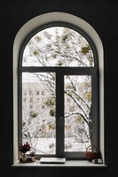 View through arch window on snowy scene. Christmas at home