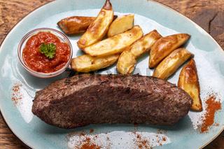 gegrilltes Steak mit Pommes auf Holz