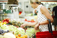 Adult woman choosing fruits in shop