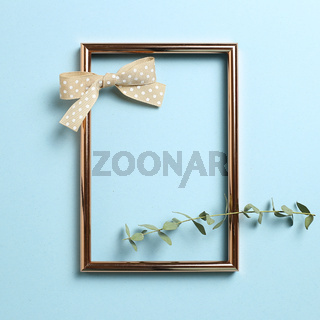 Empty photo frame with eucalyptus leaves and ribbon on sky blue background. top view, copy space
