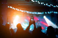 Person close up of recording video with smartphone during a concert.