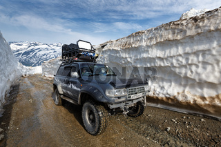 Off-road expedition car Toyota Land Cruiser driving on mountain road in snow tunnel surrounded by high snowdrifts