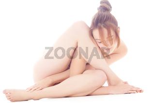 Naked gymnastic model folding herself up