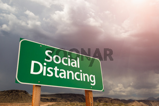Social Distancing Green Road Sign Against Ominous Stormy Cloudy Sky