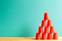 Pyramid of red plastic cups on wooden table with green background