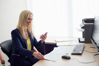 Happy business woman with phone in office