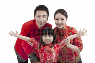 Portrait of daughter opening arms with parents,in Tang suits