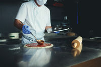 chef  with protective coronavirus face mask preparing pizza