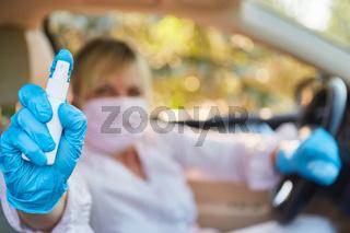 Frau im Auto mit Mundschutz und Desinfektionsmittel oder Reizgas