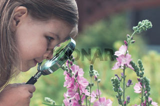 Curious girl exploring flowers with magnifying glass