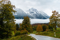 Beautiful road in the fog with view to Hochkaltermassiv. Berchtesgarden National Park, Germany