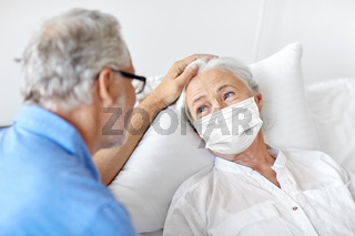 senior couple in face masks meeting at hospital