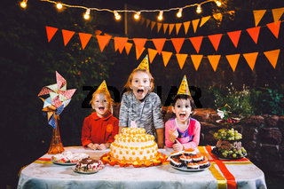 Children's birthday party. Three cheerful children girls at the table eating cake with their hands and smearing their face. Fun and festive mood in the decorated courtyard decor with bright bulbs