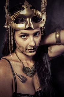 Valkyrie, Golden statue concept. Arty portrait of model with golden mask and shiny lashes. Perfect sporty body. Long hair. Profile. Performance
