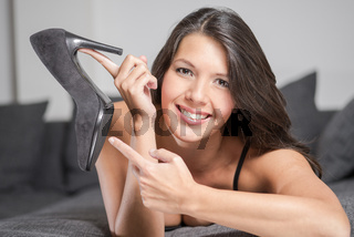 Attractive woman holding up an elegant shoe, fashion and beauty concept