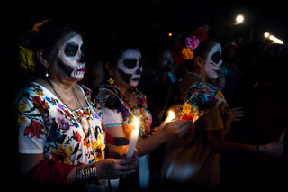 Three customed woman dressed as Catrinas with skull make-up having troubles with the candles between the people at the parade for dias de los muertos at the Festival Des Las Animas at the Cementerio General, Merida, Mexico