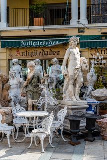 Classic sculptures and garden furniture in antique store in El Rastro