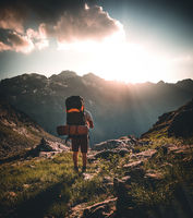 Man traveler hiking alone in breathtaking landscape of austrian Mounatins at sunset. Travel Lifestyle wanderlust adventure concept. Outdoor wilderness vacations.