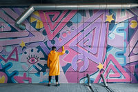 Street artist painting colorful graffiti on wall