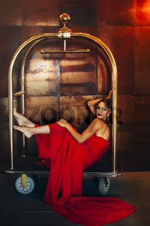 Elegant woman in red dress on luggage cart