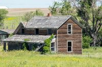 A old abandon farm house with a grass field