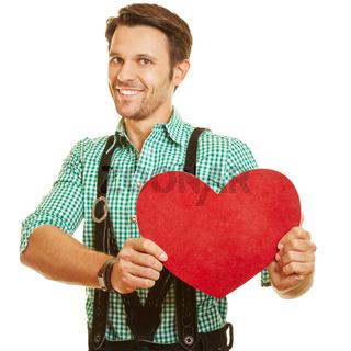 Mann in Bayern hält rotes Herz