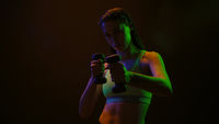Beautiful girl posing doing hand workout bicep dumbbells standing in neon lights wearing sport top stretching neck muscles turning head on black background. Neon light